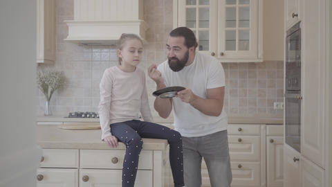 Emotional father scolding his daughter for something holding a plate in his Footage