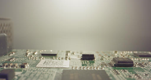 Extreme macro dolly shot of a PCB computer board with capacitors and transistors Footage