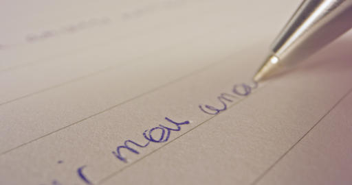 Sliding macro shot of a pen tip writing French words on paper Footage