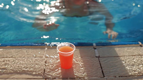 Woman swims to the edge of swimming pool, takes fresh juice, drinks it and swims Live Action