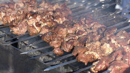 Pork barbecue cooking on metal skewers on charcoal grill with fire smoke Archivo