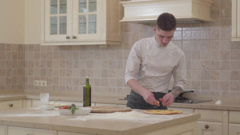 Pizza maker prepares pizza in the kitchen. Concept of food preparation Live Action