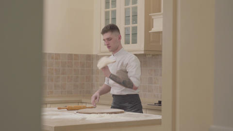Professional cook spinning and throwing pizza dough up in the air with two hands Live Action