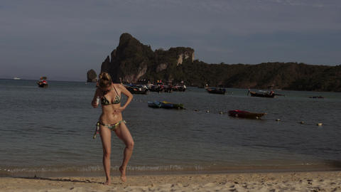 Pretty young tanned blonde woman in bikini on the sand beach. Buttering her body GIF