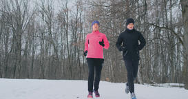 Positive beautiful young healthy couple running with sportswear through the Footage