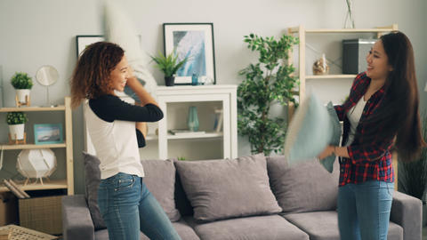Attractive girls Asian and African American are enjoying pillow fight at home Footage