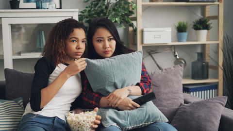 Emotional young women are watching horror film together hiding behind pillows Footage