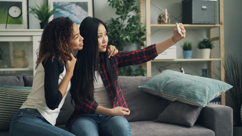 Beautiful young ladies are taking selfie with smartphone at home looking at ビデオ