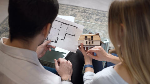 Young couple discussing blueprint and house model of future home Footage