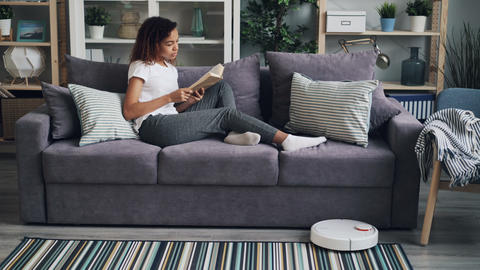 Relaxed African American girl is reading book resting on sofa while robotic Footage