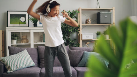 Carefree young lady African American student is having fun at home dancing and Live Action