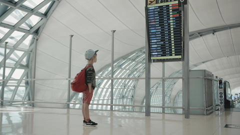 Young backpacker checking flight information on digital schedule display Footage