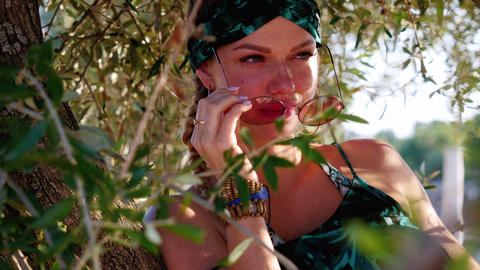 Young hippie woman with sunglasses sitting on the tree Live Action