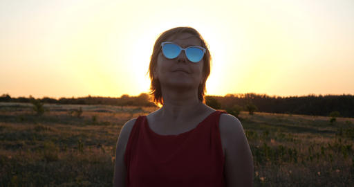 Cheery woman dancing with inspiration in a large field at sunset in slow motion Live Action