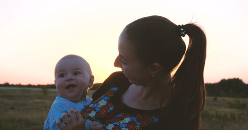 Smiling young mother and her kid enjoying life in a field at sunset in slo-mo Footage