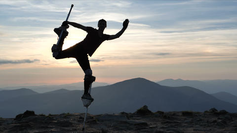 4k slow motion - man on the stilts jumps on one leg on the top of mountain Live Action