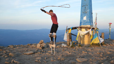 man jumps on the stilts through jumping rope on Goverla mountain Live Action