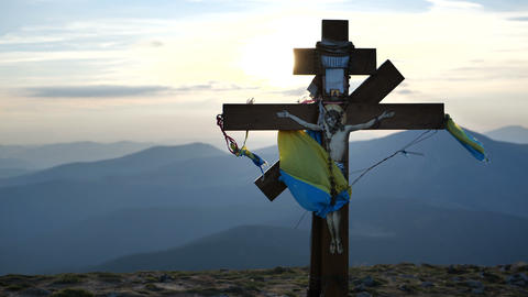 Cross with Ukraine's flag and God on it at sunset - mountain Goverla Live Action