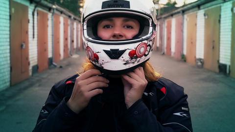 Redhead woman rider putting on motorcycle helmet. Biker Girl portrait, people Live Action