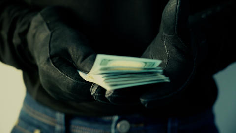 Man in black gloves holding pile of money, crime concept Footage