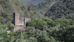 Castle in the middle of a valley with vegetation surrounding Footage