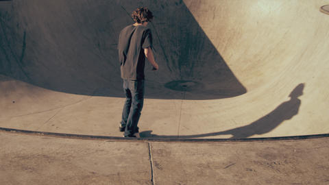 Panning shot of a skateboarder dropping in and riding around a bowl Footage
