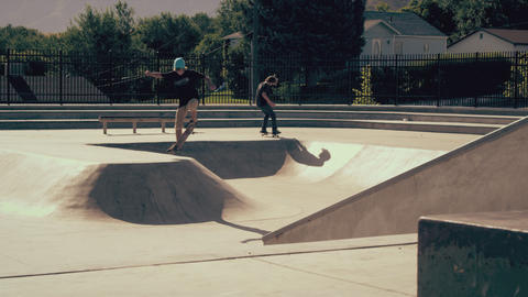 Shot of two skateboarders jumoing in and out of skatepark transition Footage