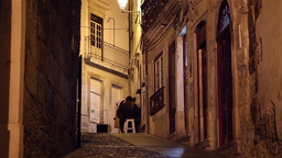 street with people walking and sitting in a bar at night in Coimbra, Portugal Footage