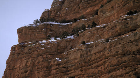 Panning shot of rocky cliffs with snow Footage