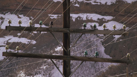 Static shot of power lines wiith snow covered mountains Footage
