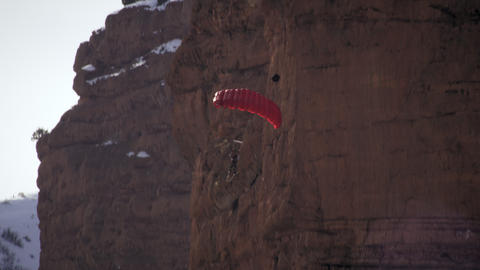 Shot of base jumper flipping with skis and opening parachute Footage