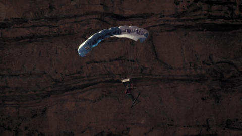 Slow motion shot of base jumper descending with open parachute Footage