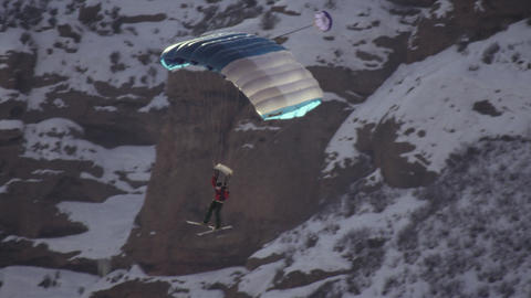 Slow-motion shot of base jumper flying through the air with open chute Footage
