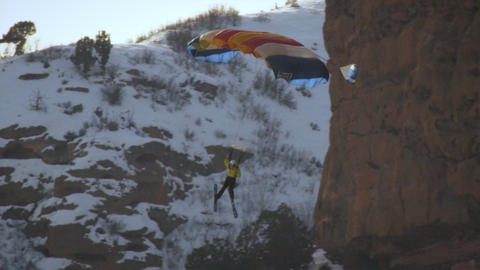 A base jumper descending a rocky mountainside in slow motion Footage