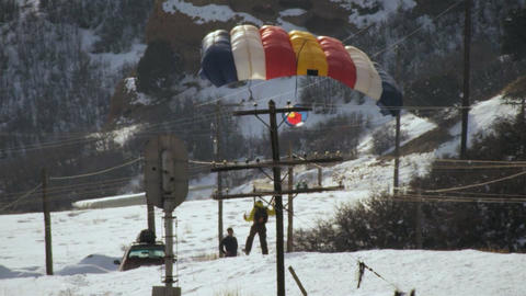 Slow motion shot of base jumper landing on snowy mountain road Footage