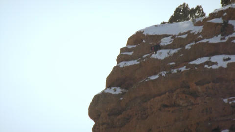 Slow-motion long shot of skiier flipping forward off snowy mountain cliff Footage