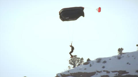 Base jumper descending just above a rocky, snowy slope in slow motion wearing sk Footage