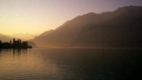 Static shot of silhouetted buildings over water at dawn Footage