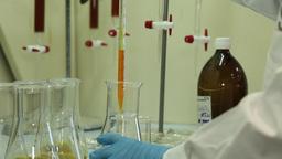scientist putting orange liquid in Erlenmeyer Flask in a laboratory, slider shot Footage