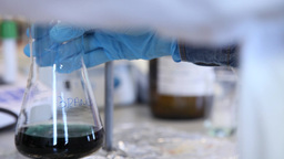 scientist shaking Erlenmeyer Flask with blue liquid in a laboratory, slider shot Footage