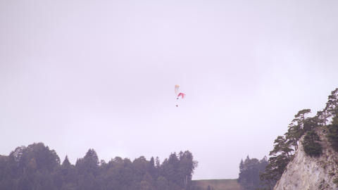 Long distance shot of two paragliders hovering over trees in Switzerland Footage