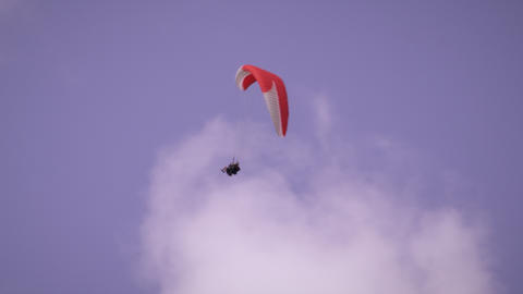 Long distance shot of two people tandem paragliding dangerously spinning in the  Live Action