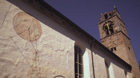 Static shot of an old church with a sundial on its wall in Switzerland Footage