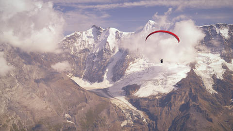 Shot of a paraglider passing the Swiss alps Footage