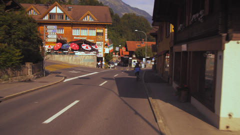 A panning shot following a bycyicle past the Alder de la Gare hotel in Brienz, S Footage