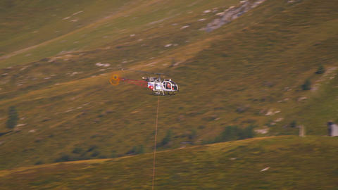 Long distance shot of a helicopter airlifting an object and flying over the hill Footage