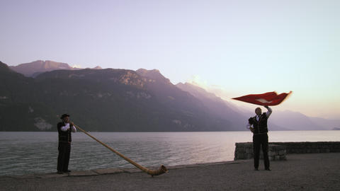 Man flourishes and throws Swiss flag while standing near alphorn player Footage