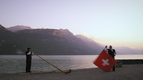 Alphorn player and flag thrower perform near lake Footage