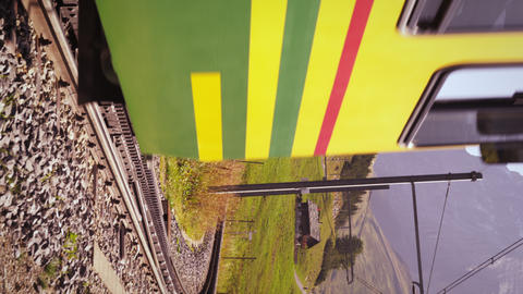 Vertical shot of a train moving on the railroad track near the alps in Switzerla Footage