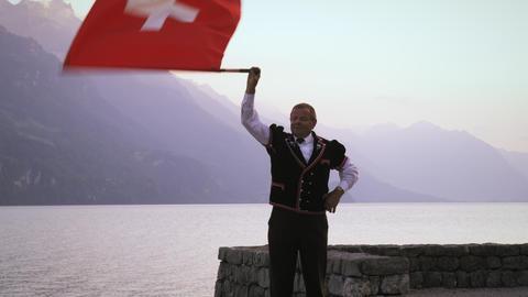 Man artfully twirls and throws Swiss flag Footage